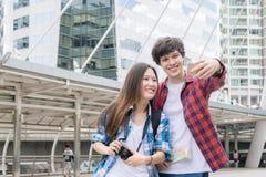 Semester- och kamratskapbegreppet Selfie som ler den asiatiska flickan och utländska pojkevänner med stadshandboken, kartlägger o Royaltyfria Bilder