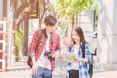 Semester- och kamratskapbegreppet som ler den asiatiska flickan och utländska pojkevänner med stadshandboken, kartlägger och vand arkivbild