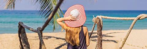 Semester på den tropiska ön Kvinna i hatt som tycker om havssikten från träbroBANER, LÅNGT FORMAT arkivfoto