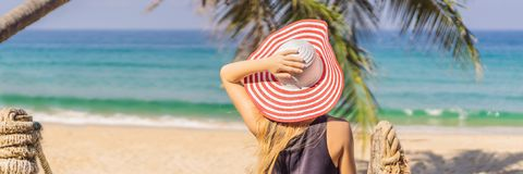 Semester på den tropiska ön Kvinna i hatt som tycker om havssikten från träbroBANER, LÅNGT FORMAT arkivfoton