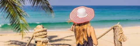 Semester på den tropiska ön Kvinna i hatt som tycker om havssikten från träbroBANER, LÅNGT FORMAT royaltyfria bilder