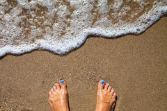 Semesterbegrepp, kvinnafot nära havsskum på guld- sand Royaltyfria Bilder