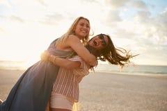 Semesterfirare för unga kvinnor som tycker om på stranden Royaltyfri Bild