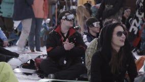 semesterorten skidar Snowboarders och skidåkare campar in Flickalönelyfthänder Manaaplaud lager videofilmer