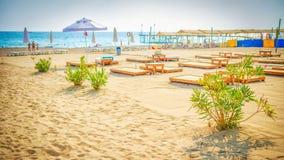Semesterortstrand med sunbeds och paraplyer Sommarsemester på blå himmel tropisk strand Royaltyfria Foton
