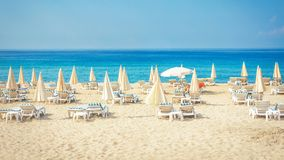 Semesterortstrand med vit sand tropisk semester för sommar Solsängar och paraplyer på stranden mot det blå havet och himmel Royaltyfri Foto