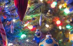 Semesterperioden julgrangarneringar glöder under lysande och livliga färgrika ljus på ett inomhus träd för liten faux Arkivbild