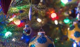 Semesterperioden julgrangarneringar glöder under lysande och livliga färgrika ljus på ett inomhus träd för liten faux Royaltyfria Bilder