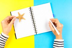 Semesterplanläggningsbegrepp Kvinnahandhandstil i öppen loppanteckningsbok över blått- och gulingbakgrund royaltyfri fotografi