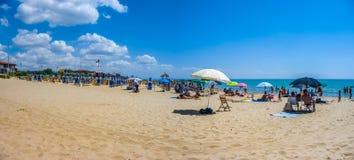 Semesterstrand med beachchairs och parasoller på en solig dag Royaltyfri Foto