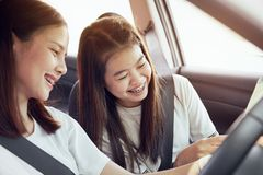 Semestertid och lopp, härlig gladlynt resor för unga kvinnor tillsammans för en avslappnande ferie Och skrattet i bilen arkivbild