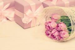 Semestra bakgrund med blommor, gåvan och det silkeslena bandet Royaltyfri Foto