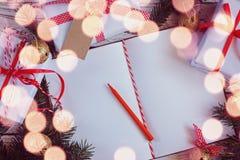 Semestra dekoranteckningsboken för meddelande med gåvan, den närvarande asken och guldklirrklockan vita röda stjärnor för abstrak Arkivfoto