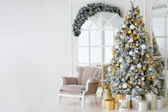 Semestra dekorerat rum med julgranen och fåtöljen royaltyfri bild