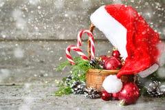 Semestra den skinande julsammansättningskorgen med bollar, leksaker, godis och sörja kottar, den Santa Claus hatten på tappningtr arkivbild