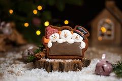 Semestra det traditionella matbagerit Roliga snowmans för pepparkaka tre i hemtrevlig varm garnering med girlandljus royaltyfri fotografi