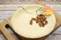 Semestra festlig bakning med en tom skorpa för bakelse för pajskal med rå pecannötmuttrar Arkivbilder