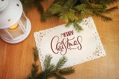 Semestra kortet, inbjudan med stearinljuset och granträdet glad text för jul Kalligrafibokstäver Royaltyfria Foton