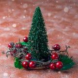 Semestra sammansättning med julträdet och kransen med järnekbär, snöeffekt, fyrkantigt format royaltyfria bilder