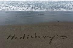 Semestrar skriftligt i sanden på stranden royaltyfri fotografi