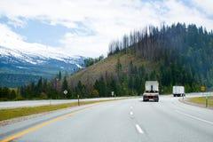 Semi перевозит двигать на грузовиках дальше поворачивая широкое шоссе с backgr гор Стоковые Фото