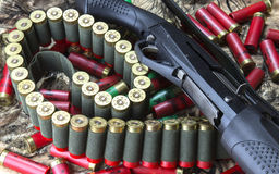 Semi-auto shotgun, 12 caliber shotgun cartridges in bandolier and stock of red and green cartridges on camouflage background. Horizontal image Royalty Free Stock Photo