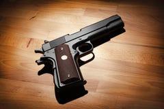Semi-automatic .45 caliber  pistol. M1911 semi-automatic .45 caliber pistol on a wooden surface. Studio shot Royalty Free Stock Image
