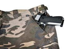 1911 semi automatic handgun in camouflage pant pocket white back. Semi automatic handgun on camouflage pant Royalty Free Stock Photography