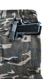 1911 semi automatic handgun in camouflage pant pocket white back. Semi automatic handgun on camouflage pant Royalty Free Stock Images