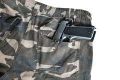 1911 semi automatic handgun in camouflage pant pocket white back. Semi automatic handgun on camouflage pant Stock Images