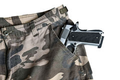 1911 semi automatic handgun in camouflage pant pocket white back. Semi automatic handgun on camouflage pant Royalty Free Stock Image