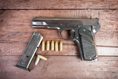 Semi-automatic 9mm gun isolated on wooden background.  Royalty Free Stock Image