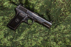Semi-automatic pistol on pixel camouflage background Stock Images