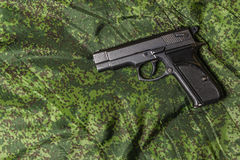 Semi-automatic pistol on pixel camouflage background Stock Image