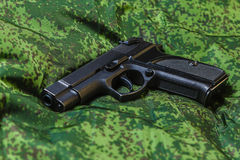 Semi-automatic pistol on pixel camouflage background Royalty Free Stock Photos