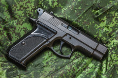 Semi-automatic pistol on pixel camouflage background Royalty Free Stock Images