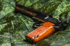 Semi-automatic silenced pistol on pixel camouflage background Royalty Free Stock Photos