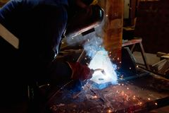 Semi-automatic welding with sparks and smoke. Closeup Stock Image