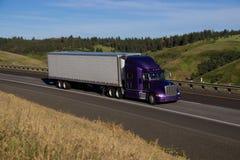 Semi-camión púrpura de Peterbilt/remolque blanco imagen de archivo