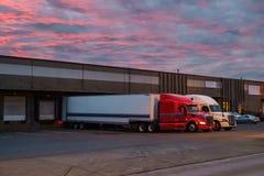 Semi caminhões na doca do frete no alvorecer Fotografia de Stock Royalty Free