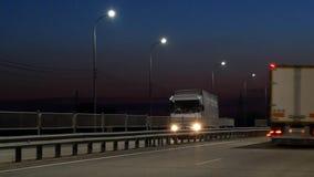 Semi caminhões no recipiente de frete levando da estrada Lanternas na noite ao longo da estrada vídeos de arquivo