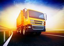 Semi-camion arancio sulla strada asfaltata confusa sotto cielo blu ed i soli Immagine Stock