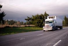 Semi camion avec l'unité de cargueur et remorque de réfrigération sur au loin salut Image stock