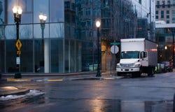 Semi camion avec la remorque de boîte dans la rue pluvieuse de ville de nuit Image stock