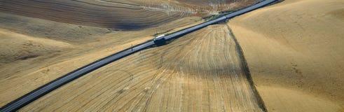 Semi-Camion che guida attraverso i campi di frumento Immagine Stock