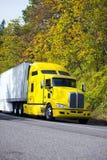 Semi camion puissant jaune avec la remorque de cargueur sur la route d'automne Photos stock