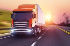Semi-camion sur une route dans le coucher du soleil Photo stock