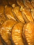 Semi circle shape golden brown pastry. Nicely arranged on tray in a pastry shop Stock Image