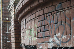A semi-circular wall of red bricks with painted graffiti. Old ancient auld olden time-worn relief masonry setting placing Royalty Free Stock Photography