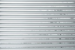 Semi-closed metallic blinds on a window Royalty Free Stock Photos
